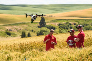 Dr. Arron Carter with students flying a drone in a wheat field